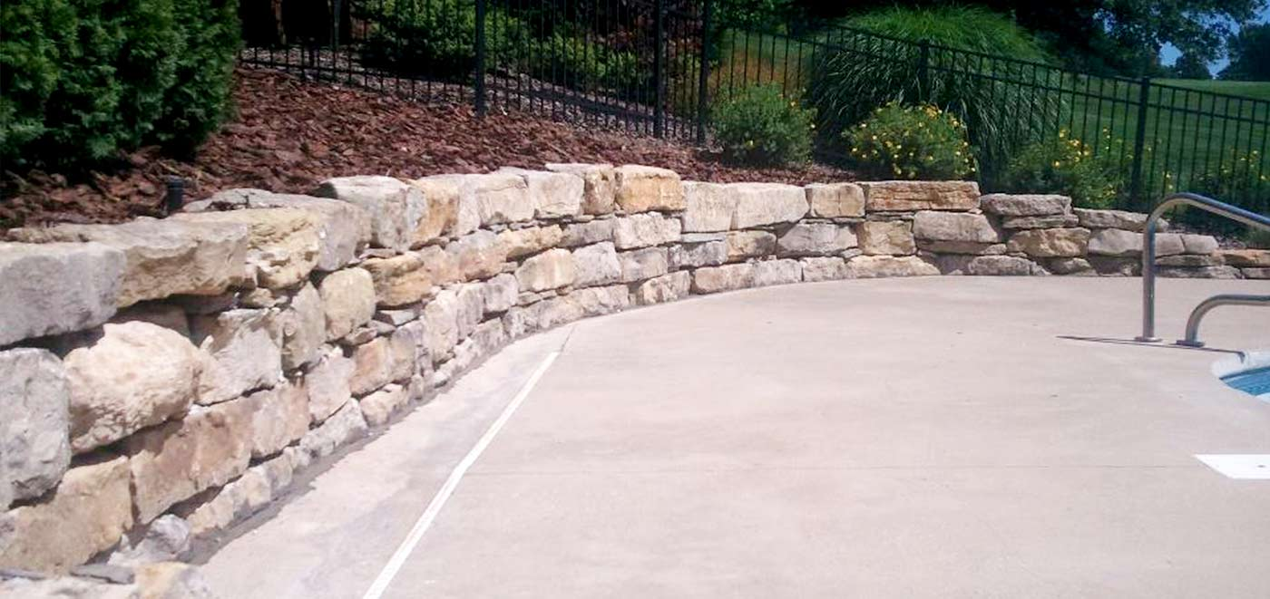 Stone Wall Surrounding Pool Landscaping